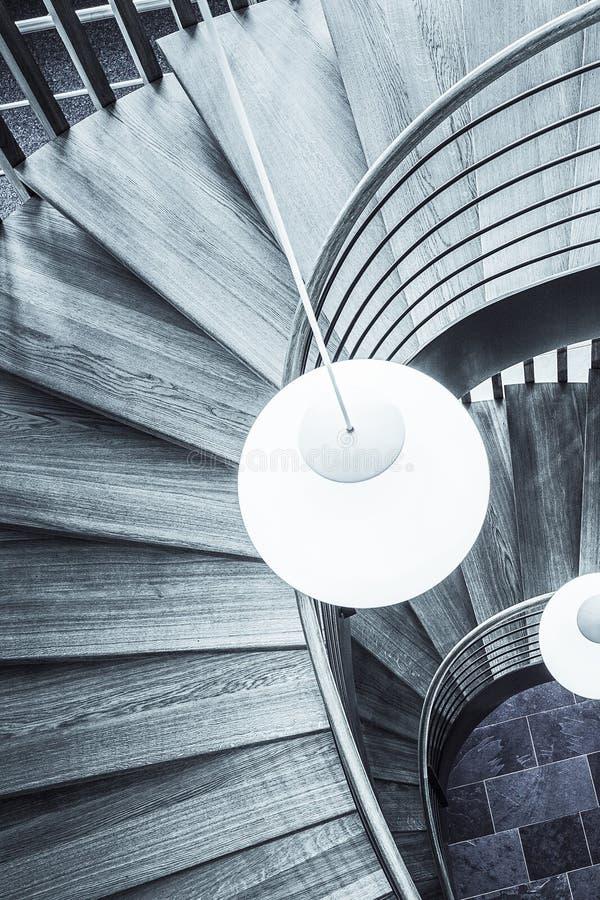 Biała lampa nad drewnianym ślimakowatym schody przy biurem obraz royalty free