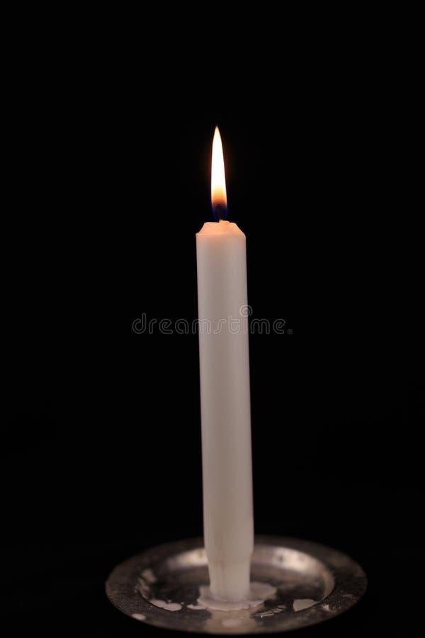 Biała płonąca świeczka na czarnym odosobnionym tle fotografia royalty free