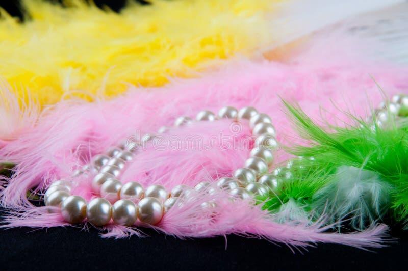 Biała perl kolia kłaść w kolorowych piórkach i czerń stole fotografia stock