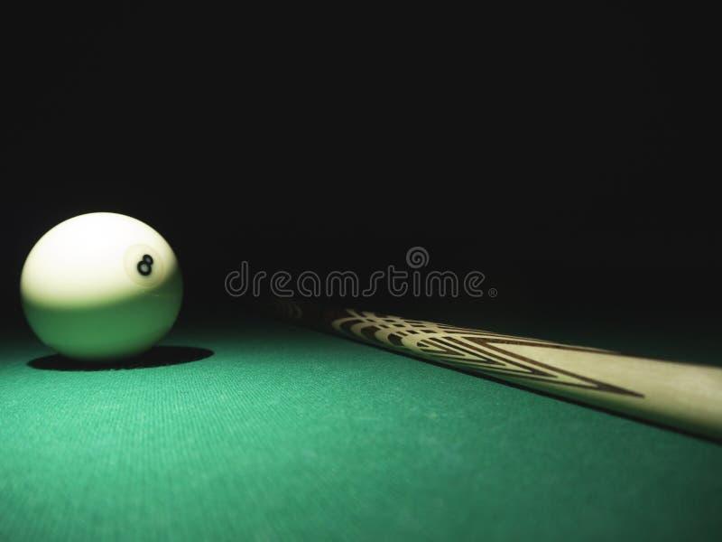 Biała piłka liczba 8 od rosyjskiego bilardowego ostrosłupa i wskazówka na stole Czarny t?o obrazy stock