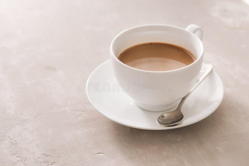 Biała porcelanowa filiżanka herbata z mlekiem na prostym tle zdjęcia royalty free