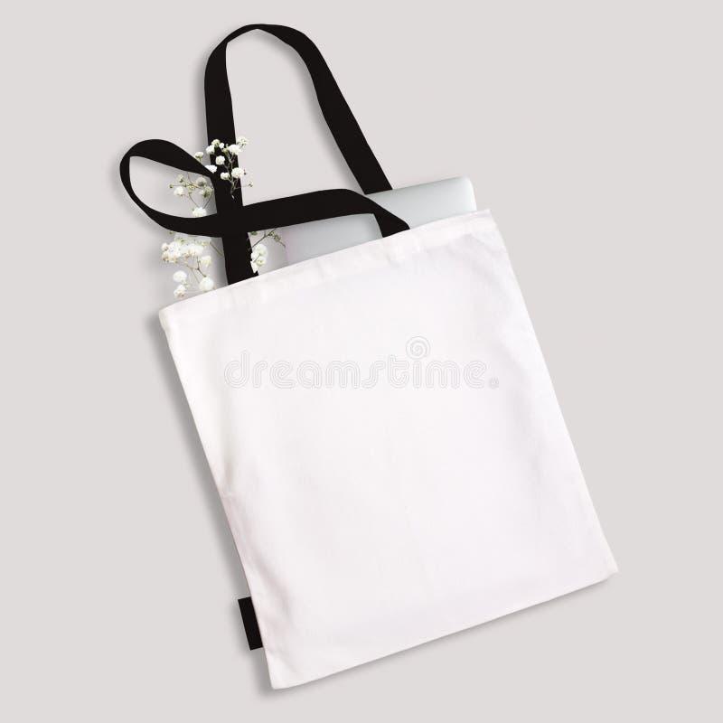 Biała pusta bawełniana eco dużego ciężaru torba z czerni patkami, małą etykietka, laptop i kwiaty, inside Projekta mockup obraz stock
