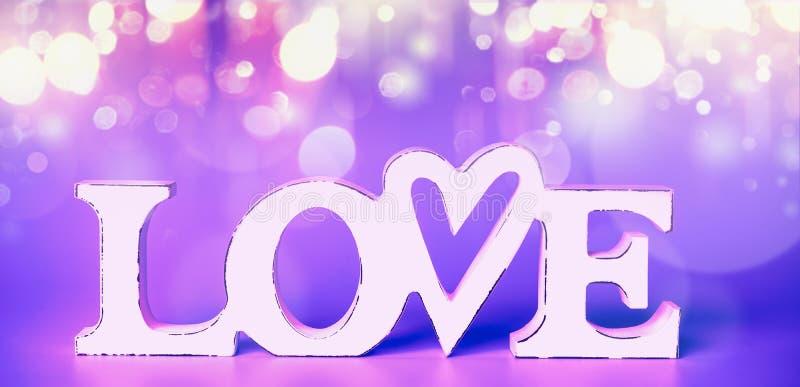 Biała słowo miłość przy neonowym koloru tłem z świątecznym partyjnym bokeh fotografia royalty free