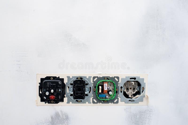 Biała stiuk ściany tekstura ten otwarci elektryczni ujścia i zmiany zdjęcia stock