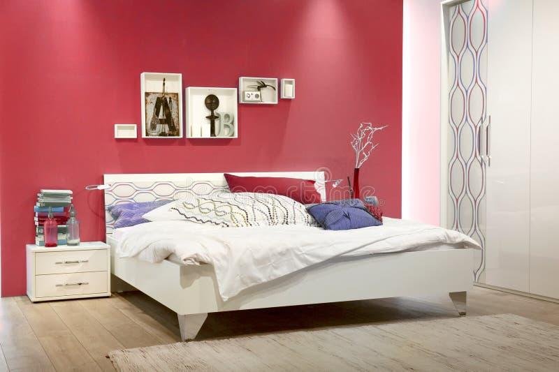 Biała sypialnia z czerwieni ścianą zdjęcie stock