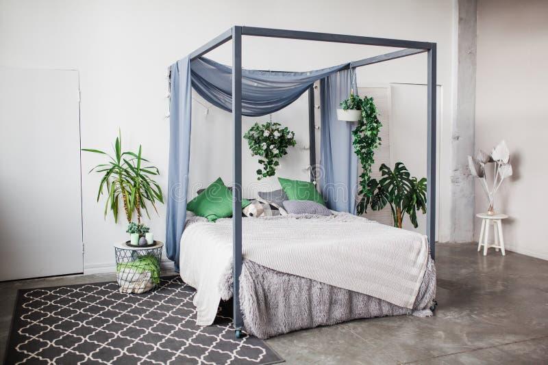 Biała sypialnia z prostymi wystrój rzeczami w plaża projektującym domowym mieszkaniu z greenery, dom rośliny fotografia royalty free