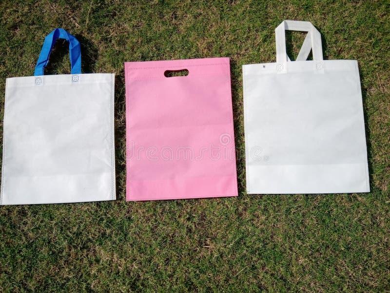 biała torebka na uchwyt z różowym kolorem, przecięte torby przyjazne dla środowiska, torby na trawie z włókniną zdjęcia stock