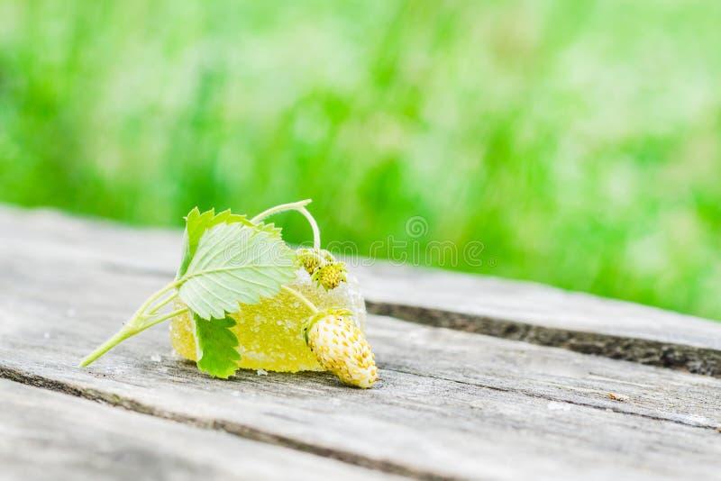 Biała truskawka z zieleń liśćmi i kawałkiem żółty marmoladowy na starym szarym drewnianym stole na zielonym tle obrazy stock