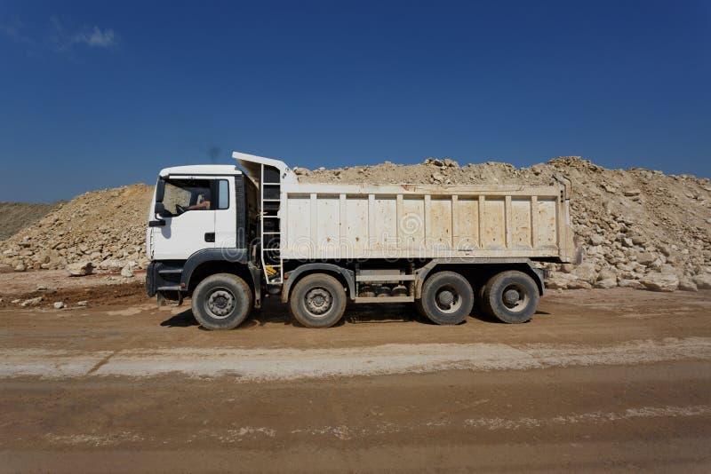 Biała usyp ciężarówka, ciężarówka pełno kamienie w piaska łupie, odtransportowywać materiały na naturalnym tle zdjęcie royalty free