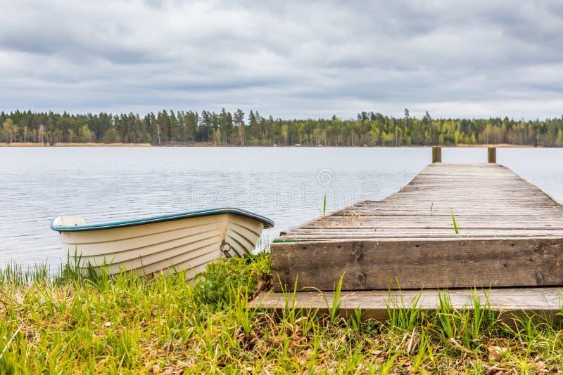 Biała Wioślarska łódź Obok Drewnianego mola zdjęcie stock
