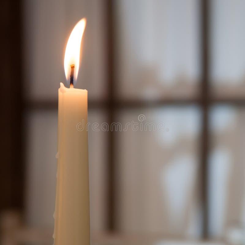 Biała wysoka płonąca świeczka na tle okno zdjęcie stock