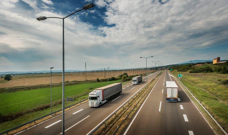 Białe ciężarówki przechodzi - autostrada ruch drogowy fotografia stock