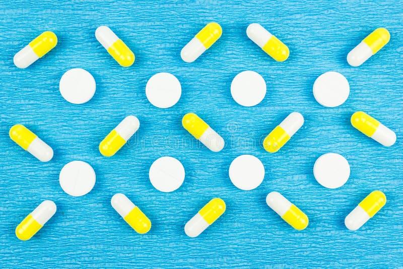 Białe i żółte pigułki na błękitnym tle obraz royalty free