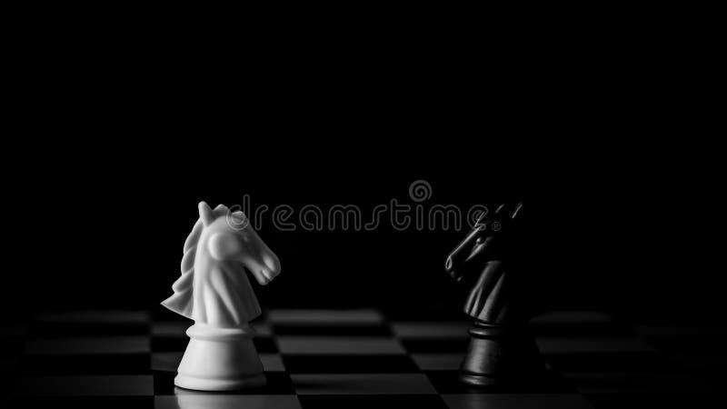 BiaÅ'e i czarne szachy na szachownicy w ciemnym tle zdjęcie stock