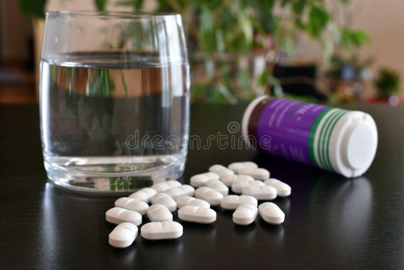 Białe pigułki z szkłem woda i butelka, antybiotyki, antidepressants zdjęcia stock