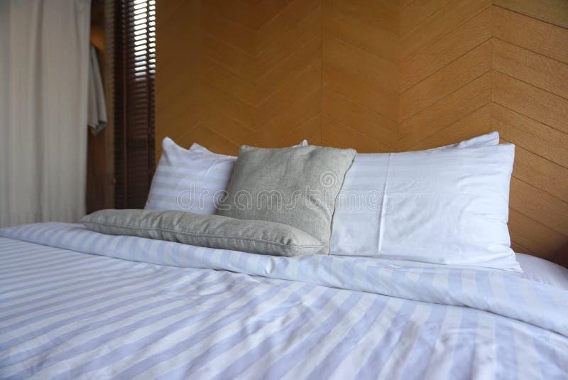 Białe poduszki i jasnopopielata rzut poduszka na białym łóżkowym prześcieradle z szalunku tłem zdjęcie stock