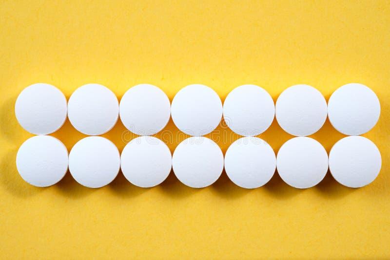 Białe round farmaceutyczne pigułki na żółtym tle fotografia stock