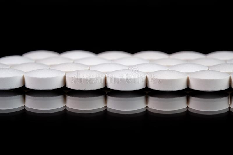 Białe round farmaceutyczne pigułki na odbijającej powierzchni, czarny tło obrazy stock