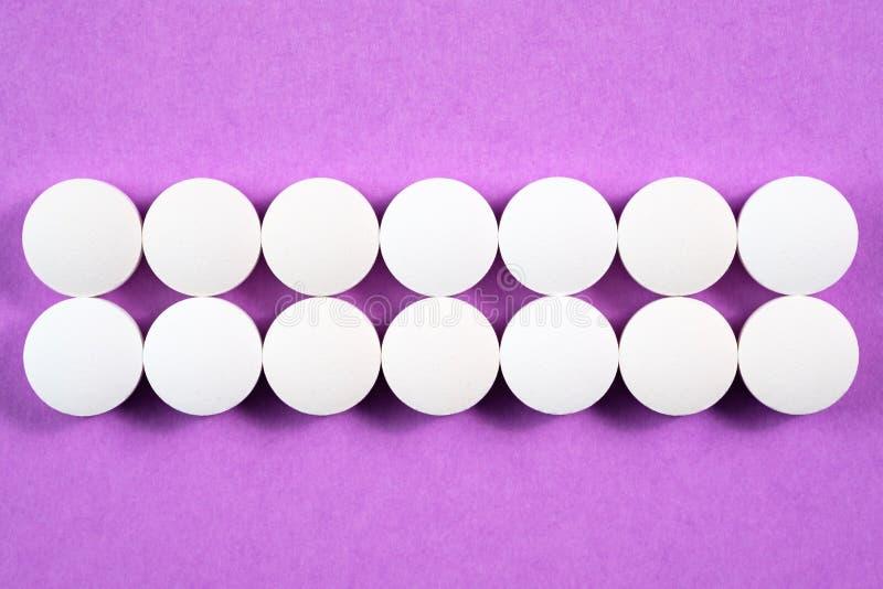 Białe round farmaceutyczne pigułki na różowym tle fotografia stock