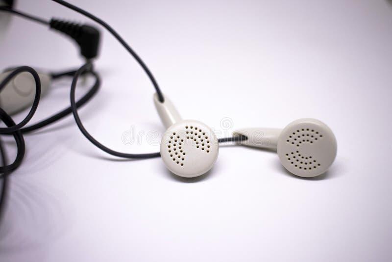 Białe słuchawki na białym tle Koncepcja muzyki cyfrowej Zbliżenie zdjęcia stock