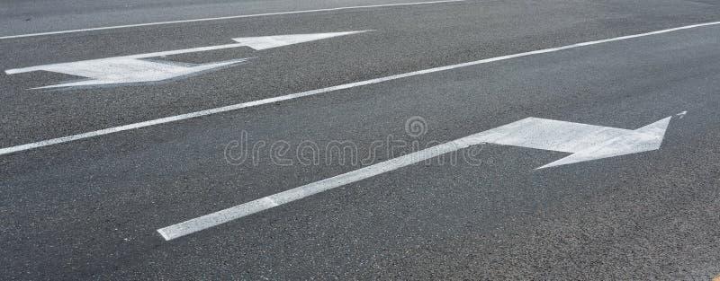 Białe strzały wskazuje kierunku Wykonawczego drogowego znaka przechodzą w kierunku wskazującym strzałkowatym ruchem drogowym fotografia royalty free