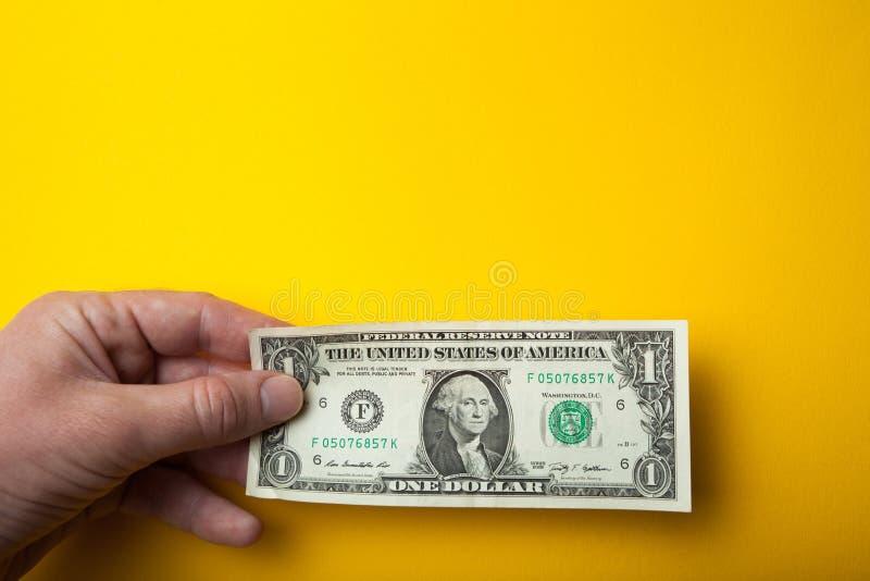Białego człowieka ręka trzyma jeden dolara, pusta przestrzeń dla teksta zdjęcia stock