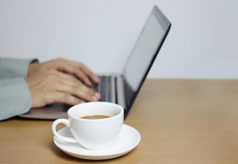 białego kawowego kubka i komputeru notatnik na brąz drewnianej podłodze zdjęcie stock