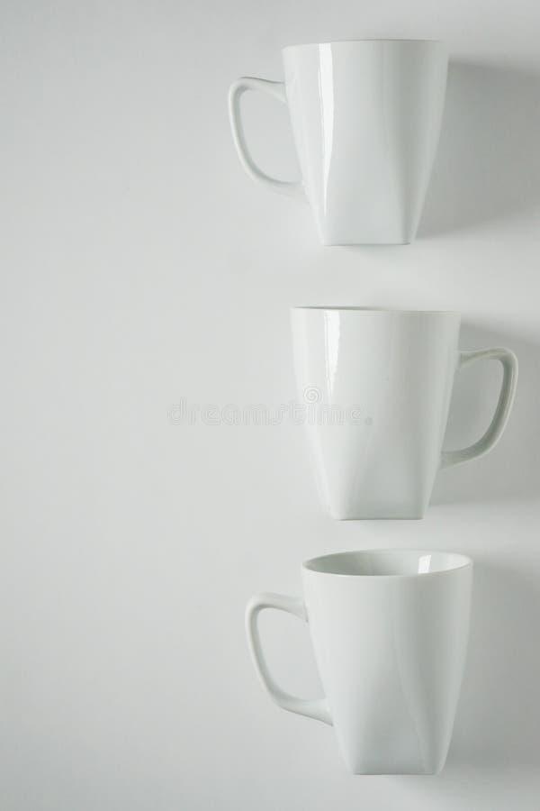 3 białego kawowego kubka na białym tle w pionowo rzędzie, pusta kopii przestrzeń obraz royalty free