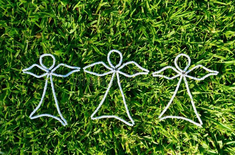 3 białego koralika anioła na świeżo skoszonym zielonej trawy tle brać od above fotografia royalty free