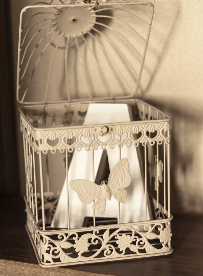 Białego metalu klatka z motylem i pisze list a zdjęcia stock