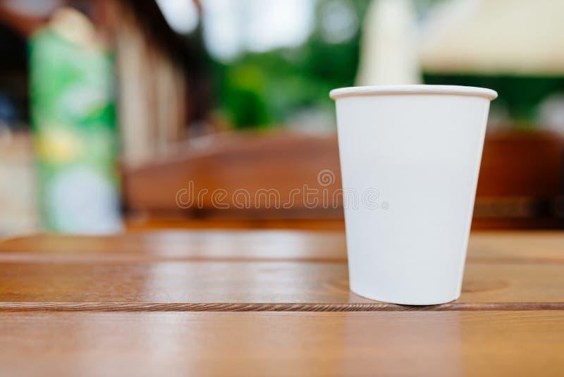Białego papieru filiżanka na drewnianym stole outdoors fotografia stock