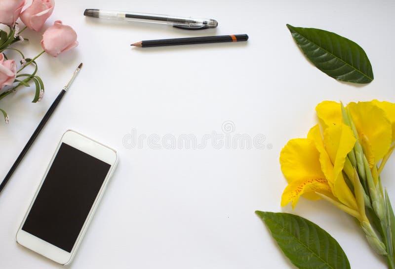 Białego papieru tło z kwiatami i liśćmi Projektanta miejsce pracy z smartphone zdjęcia royalty free