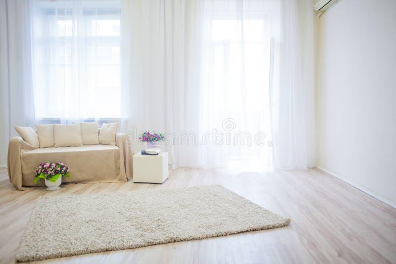 Białego pokoju kanapy beż rezerwuje i kwitnie zdjęcie stock