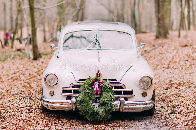 Białego rocznika ślubny samochód dekorował z wiankiem w jesień lesie obraz royalty free