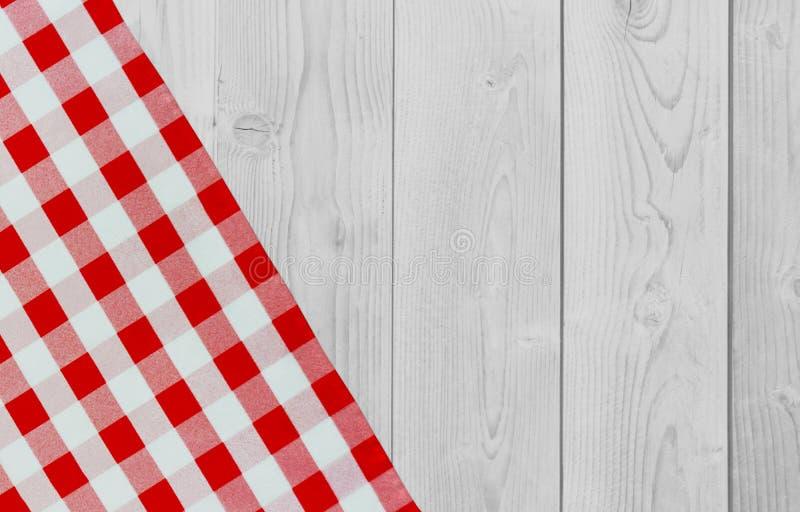 Białego rocznika drewniany stół z czerwoną checker pieluchą W kratkę tkanina i drewniany lekki tło Dekoracja kuchenny ręcznik stó obraz royalty free