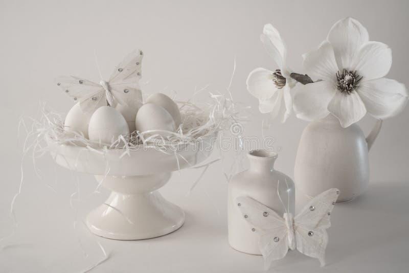 Białego rocznika Wielkanocna scena, torta stojak z jajkami, wazy, kwiaty, przeciw białemu tłu obraz royalty free