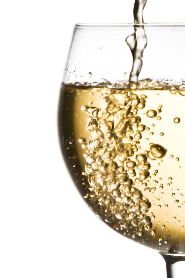 Białego wina dolewanie w przyrodniego szkło z przestrzenią dla teksta obrazy stock
