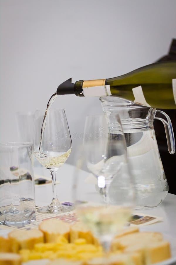 Białego wina Sauvignon blanc nalewa w wineglass podczas wina testowanie w wino sklepie zdjęcia royalty free