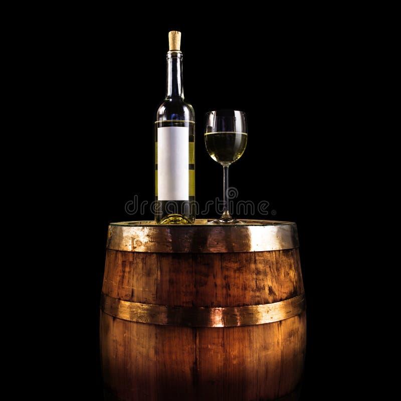 Białego wina szkło na drewnianej baryłce i butelka - odizolowywającej na czerni obrazy stock