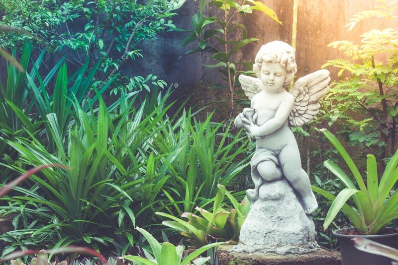 Białej amorek rzeźby, statuy pozycja w plenerowym ogródzie otaczającym z zielony naturalnym lub obraz stock