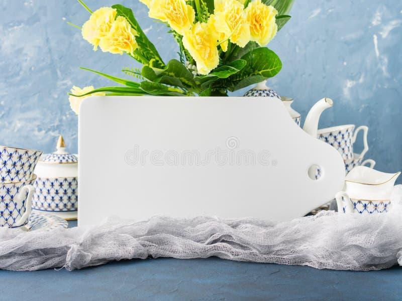Białej deski egzamin próbny w górę herbacianego setu i wielkanocy kwitnie obraz stock