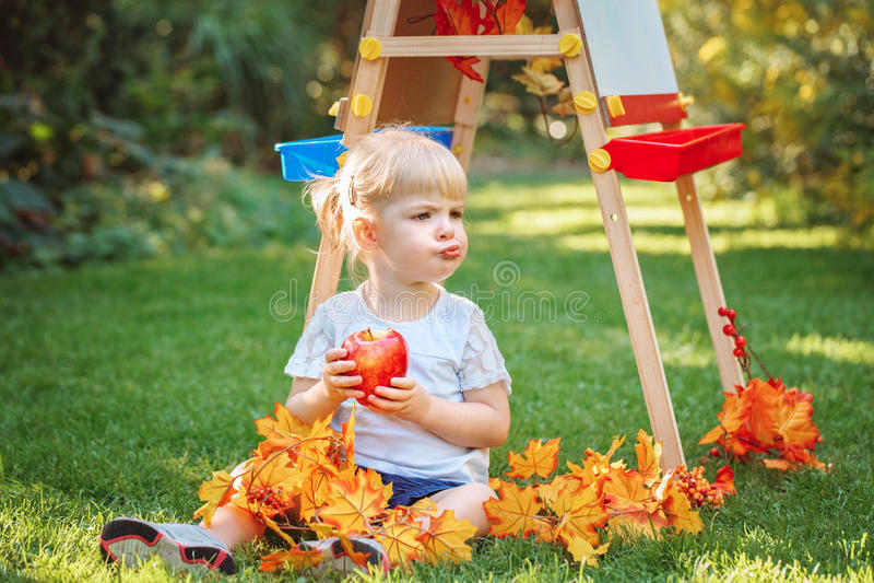 Białej Kaukaskiej berbecia dziecka dzieciaka dziewczyny siedzący outside w lato jesieni parku rysunek sztalugi łasowania jabłczan zdjęcie stock
