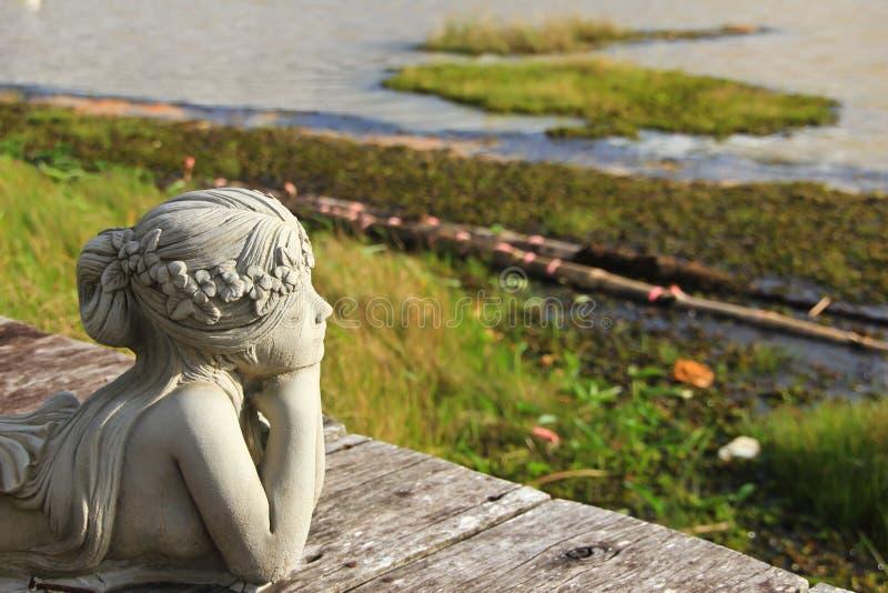 Białej kobiety statua patrzeje jezioro obraz stock
