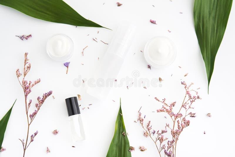 Białej kremowej butelki umieszczający, Pusty etykietka pakunek dla egzaminu próbnego up na zielonym ulistnienia tle, i kwiaty Poj obraz royalty free