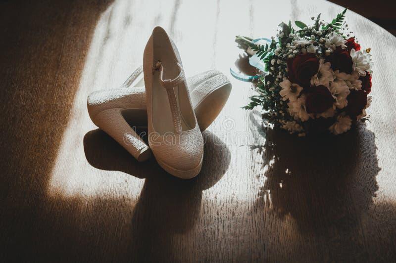 Białej skóry ślubu buty na szpilkach i panny młodej bukiet na drewnianej podłodze w słońc światłach Elegancki i romantyczny fotog zdjęcie stock