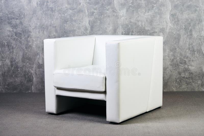 Białej skóry biurowy krzesło w pustym pokoju z szarą tekstury ścianą obrazy royalty free