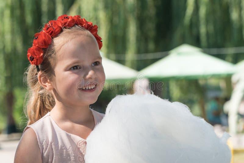Białoruś, Gomel, na Marzec 10, 2018 Dzieci wakacyjni przy otwarciem sklep karawana Dziewczyna je słodką powiewną bawełnę zdjęcie stock