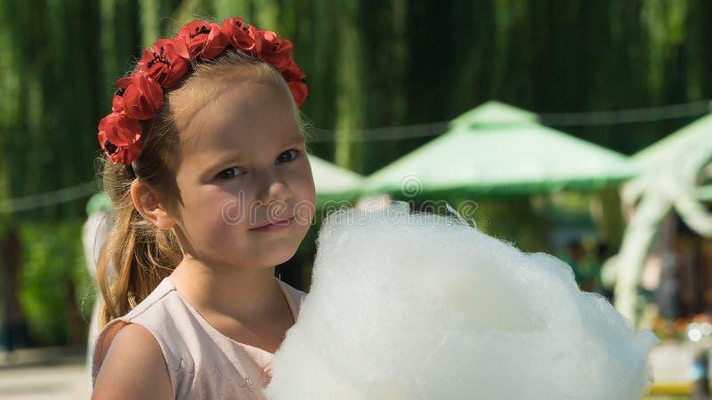 Białoruś, Gomel, na Marzec 10, 2018 Dzieci wakacyjni przy otwarciem sklep karawana Dziewczyna je słodką powiewną bawełnę obraz stock