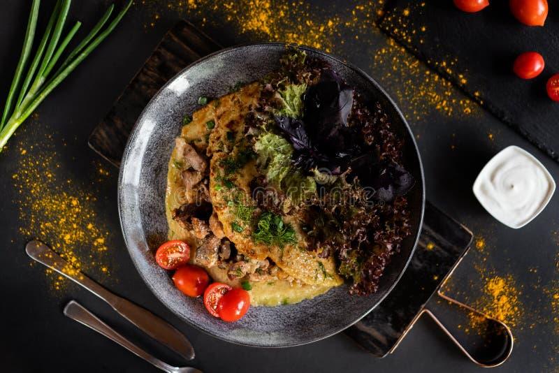Białoruski Krajowy jedzenie - draniki Tradycyjny łasowania pojęcie Ciemny tło z talerzem z blinem z mięsem z warzywami obrazy stock