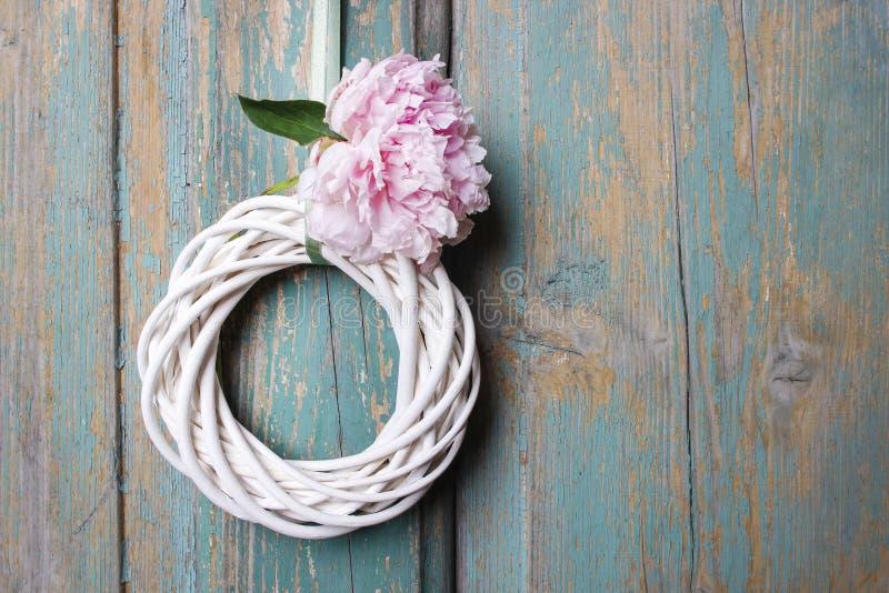 Biały łozinowy wianek na drewnianym drzwi fotografia stock